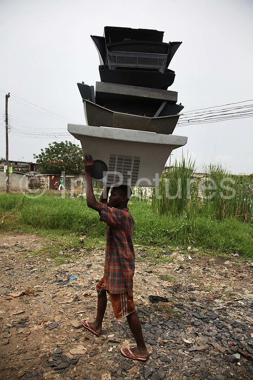 A young boy is carrying plastic TV casings, walking along a path covered with broken CRT TV glass.  Alaba International Market, one of the largest markets for electronic goods in West Africa.  New and old - and a lot of non-working electronic goods such as TVs and computers come in to the market via Lagos harbour from the US, Western Europe and China.This picture is part of an undercover investigation by Greenpeace and Sky News.  A TV-set originally delivered to a municipality-run collecting point in UK for discarded electronic products was tracked and monitored by Greenpeace using a combination of GPS, GSM, and an onboard radiofrequency transmitter placed inside the TV-set.  The TV arrived in Lagos in container no 4629416 and was found in Alaba International Market and bought back by Greenpeace activist. The TV was subsequently brought back to England and used as proof of illegal export of electronic waste. A number of individual are currently on trial in London in connection with illegal exports(Nov 2011)