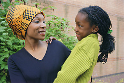 Mother standing outdoors holding young daughter smiling,