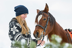 Teenage girl with horse in farmland during winter, Bavaria, Germany
