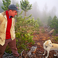 A hiker and his dog walk along a foggy road in the Wind River Range near Lander, Wyoming.