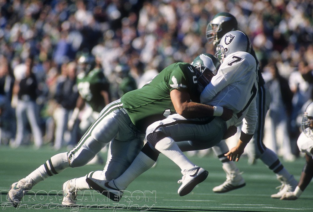 Philadelphia Eagles nose tackle Mike Golic (90) levels Los Angeles Raiders quarterback Steve Beuerlein during an NFL football game, Sunday, Oct. 22, 1989 at Veterans Stadium in Philadelphia, Pa. The Eagles won, 10-7. (Photo by D. Ross Cameron)