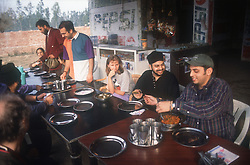 Group of tourists eating food in roadside café in India,
