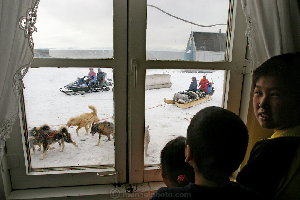 Seal hunter Emil Madsen's children, Abraham, Martin and Belissa break away from watching MTV to watch dogsled teams and travelers on a skidoo hauling supplies in a sled pass by the window of their house in Cap Hope, Greenland. (From the book What I Eat: Around the World in 80 Diets.)