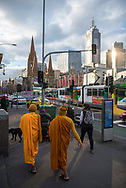 Two Buddhist in religious attire walk on St. Kilda Road outside Flinders Street Station in the center of Melbourne, Australia.