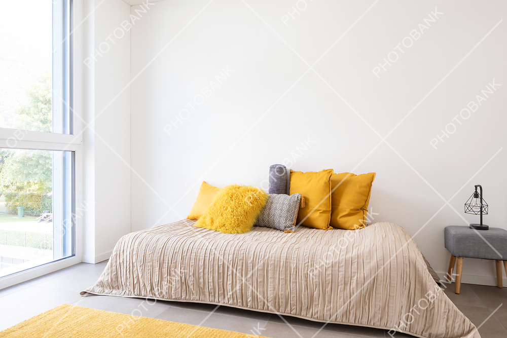 Nice bedroom with a bed, sidetable and lots of pillows. Detail of the bed with a large white wall, perfect for copy space. Very romantic room. Concept