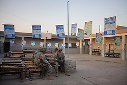 Members of the 1st Infantry, 17th Regiment, take a break at a local polling station the day before elections, Mosul, Iraq, Dec. 14, 2005. They are helping Iraqi forces patrol western Mosul as part of an effort to provide security in preparation for Iraq's first post-Saddam parliamentary elections. The western sector is home to Mosul's primarily Sunni population, which has been resistant to the American presence in Iraq.