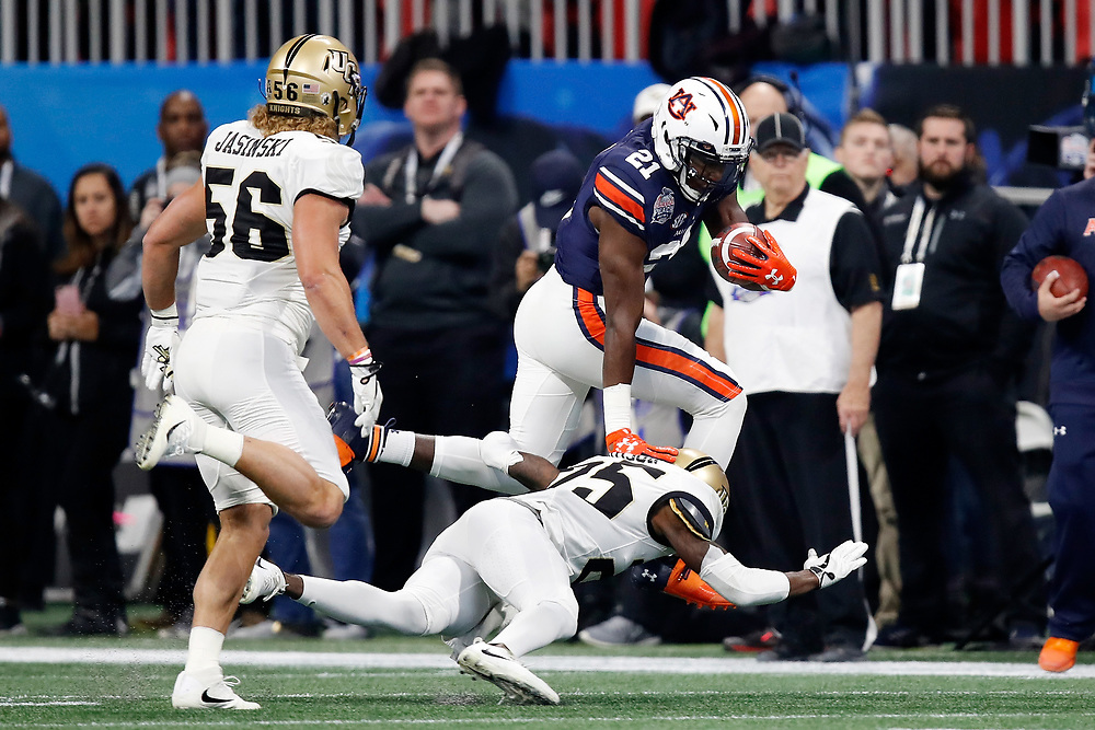 Auburn Tigers running back Kerryon Johnson (21) stiff arms UCF Knights defensive back Kyle Gibson (25) during the 2018 Chick-fil-A Peach Bowl NCAA football game on Monday, January 1, 2018 in Atlanta. (Paul Abell / Abell Images for the Chick-fil-A Peach Bowl)