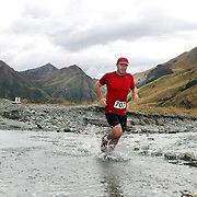 Runner  Guy Blundell crosses Moke Creek on the Ben Lomond High Country Station during the Pure South Shotover Moonlight Mountain Marathon and trail runs. Moke Lake, Queenstown, New Zealand. 4th February 2012. Photo Tim Clayton
