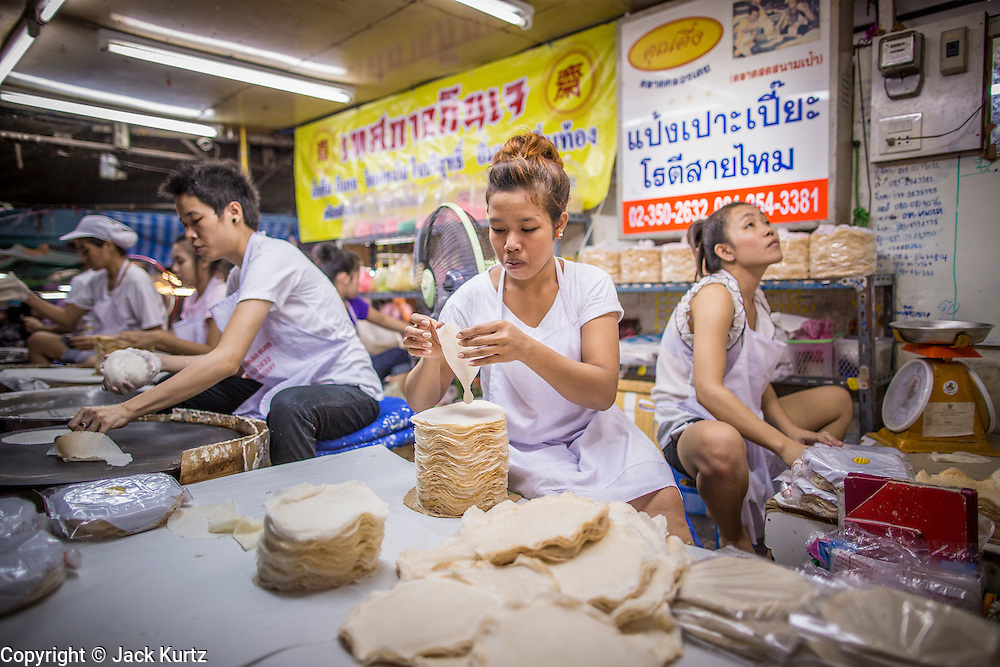 """03 OCTOBER 2012 - BANGKOK, THAILAND:  Women make roti, a very light and delicate type of flat bread in Khlong Toey Market in Bangkok. Khlong Toey (also called Khlong Toei) Market is one of the largest """"wet markets"""" in Thailand. Thousands of people shop in the sprawling market for fresh fruits and vegetables as well meat, fish and poultry every day.      PHOTO BY JACK KURTZ"""