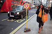 Temporary bus stop on a busy Oxford Street in London, England, United Kingdom. Buses and taxis pass as a woman checks her mobile phone.