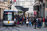 Busy tram stop Korenmarkt 1 with many passengers getting on or off the route 1 De Lijn electric tram to Flanders Expo in the city centre of Ghent, Belgium.