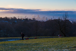 """A runner and his dogs on Hampstead Heath with The City's skyline in the background. The threatened snow from """"The Beast From The East"""" weather system doesn't materialise overnight in London leaving a crisp, clear morning, seen from Hampstead Heath in North London. London, February 27 2018."""