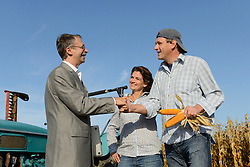 Farmer couple and businessman shaking hands in cornfield, Bavaria, Germany