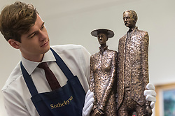 "© Licensed to London News Pictures. 16/11/2018. LONDON, UK. A technician examines ""The Settlers"", 2001, by Rowan Gillespie (Est. GBP15,000-20,000). Preview of ""A Living Legacy"", the Irish Art Collection of Brian P. Burns, a collection spanning artists from the 18th century to the present day.  Over 100 works will be offered for sale on 21 November at Sotheby's in London.  Photo credit: Stephen Chung/LNP"