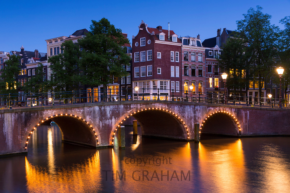 Illuminated bridge at corner of Kaisersgracht and Leidsegracht in the canal ring area of Jordaan district, Amsterdam, Holland