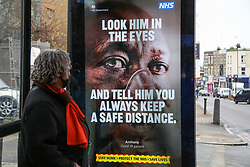 © Licensed to London News Pictures. 01/02/2021. London, UK. A woman looks at the government's 'Look him in the eyes - And tell him you always keep a safe distance.' awareness publicity campaign poster in north London.  Covid-19 infection rates are continuing to drop across London. According to a Government scientific adviser, the UK could be easing out of restrictions in March and back to almost normal by summer if vaccines are 70 to 80 per cent effective at blocking transmission. Photo credit: Dinendra Haria/LNP