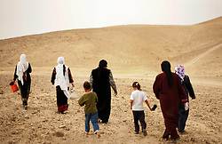 Bedouin women walk back to their homes after visiting the Rashaida family's newborn baby, Bethlehem, Palestinian Territories, Nov. 16, 2004. It is customary for the family to receive many guests for the first for ten days after the birth. The family's eighth child was born in a small village outside of Bethlehem, on the day of Yasser Arafat's death.