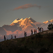 At sunset, childern play football in front of a view of Nanda Devi, the highest mountain located entirely within the country