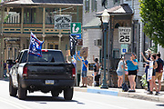 A truck with a Molon Labe flag and an American flag flying from the tailgate drives through the Mifflinburg Pride Event.