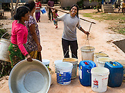 03 JUNE 2016 - SIEM REAP, CAMBODIA: People set out their water jugs at a water distribution point in Sot Nikum, a village northeast of Siem Reap. Wells in the village have been dry for more than three months because of the drought that is gripping most of Southeast Asia. People in the community rely on water they have to buy from water sellers or water brought in by NGOs. They were waiting for water brought in by truck from Siem Reap by Water on Wheels, a NGO in Siem Reap. Cambodia is in the second year of  a record shattering drought, brought on by climate change and the El Niño weather pattern. There is no water to irrigate the farm fields and many of the wells in the area have run dry.     PHOTO BY JACK KURTZ