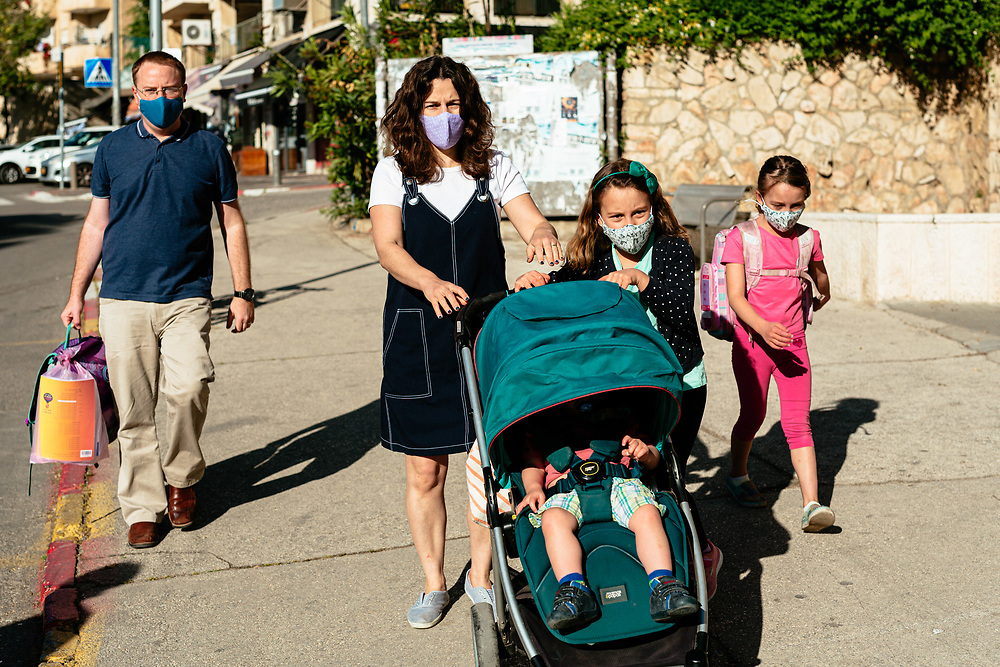 Twin girls Clil (R) and Alma (2nd R), their brother Ofek, and parents Anna and Matti Michel, are seen as they walk towards the elementary school where the girls study, in Jerusalem, Israel, on May 3, 2020.