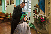 Father Michael Branch lights a candle wearing protective gloves before delivering mass to parishioners via live-stream at on 27th March 2020 at St Peters Roman Catholic Church in Woolwich, London, United Kingdom. Following the governments advice on social distancing, the Catholic Church has suspended public worship until further notice to help slow the spread of the Coronavirus. Designed by Augustus Pugin in 1841-42 in the style of the Gothic Revival, St Peters RC,  is one of only three Pugin churches in London. In 1883 St Peter the Apostle Roman Catholic Church opened, the first to do so in London, following the Reformation.