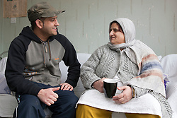 Portrait of South Asian woman and her son sitting talking.