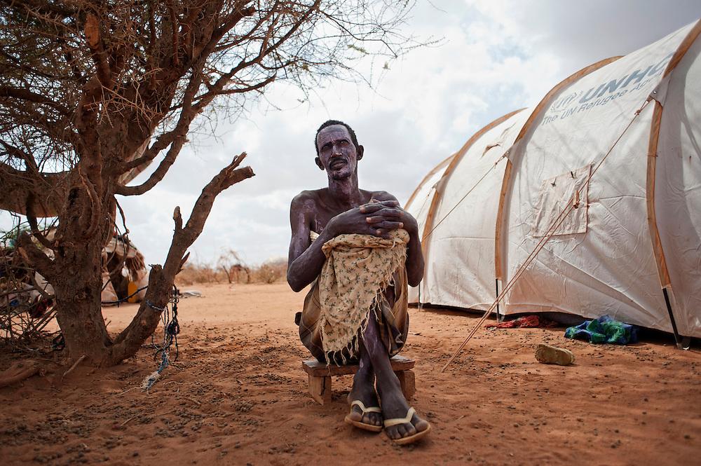 Kenya, camp de réfugiés de Dadaab - Ifo 3. Hassan Abdi Yere, 48 ans, de Boualey. Ce fermier nomade n'était pas bien riche, déjà en Somalie. Il élevait un cheptel de 80 vaches qui a succombé à cette troisième année de sécheresse. Sans ressources, Hassan a rejoint Dadaab il y a 20 jours où il a contracté le virus de la rougeole. Une épidémie sévit en ce moment dans le camp, alertant des ONG comme Médecins Sans Frontières. Une nouvelle campagne de vaccination a visé non plus seulement les enfants, mais aussi les populations de moins de trente ans.                           Depuis sept jours, Hassan est fiévreux, il a des crampes à l'estomac, il ne ferme plus l'oeil de la nuit. Il essaie de prendre des douches pour se refroidir, mais les points d'eau sont loin. Grâce au traitement qu'il respecte scrupuleusement, il reprend des forces petit à petit, ses douleurs s'estompent.