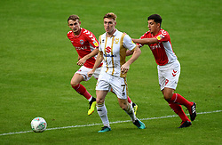 Milton Keynes Dons' Ryan Watson (centre)  and Charlton Athletic's Albie Morgan (right) and Charlton Athletic's Taylor Maloney (left) battle for the ball