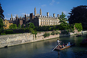 Punts and passengers glide past The Clare College (founded 1326) on the River Cam past the Garret Hostel bridge, Cambridge, UK