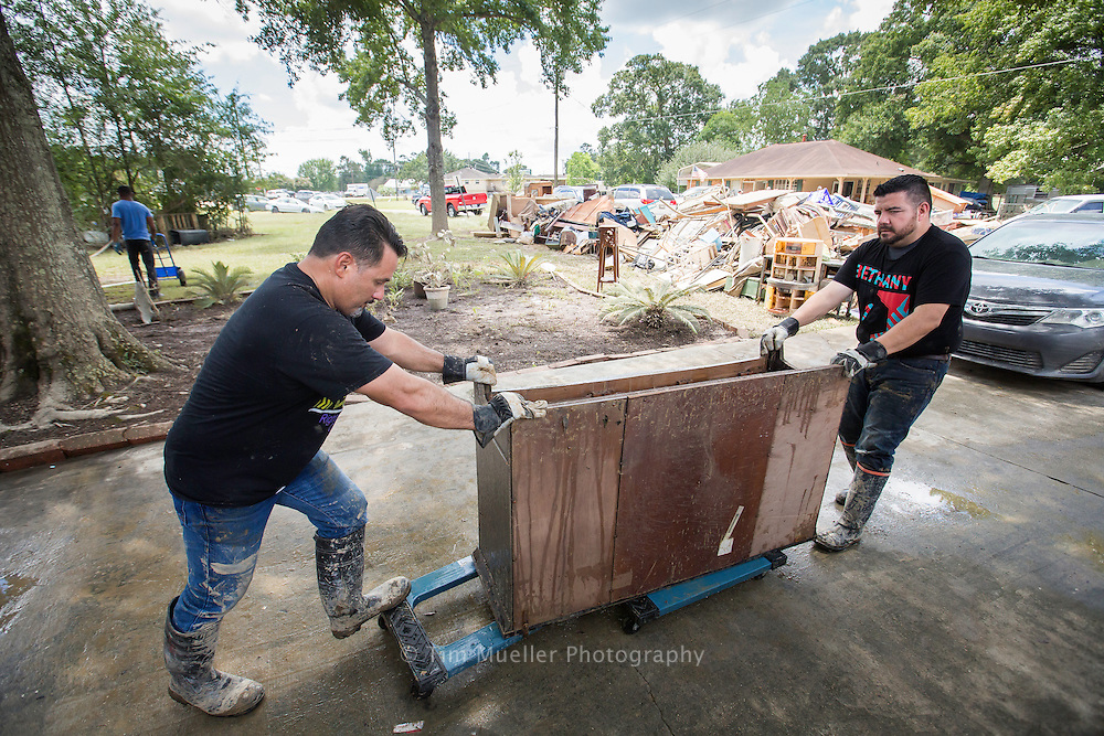 Volunteers, from left, Luis Marin and Pastor Gus Desiga of New Beginnings Christian Church in Mercedes, TX roll furniture to the curb Thursday, August 18, 2016. Members of New Beginnings Christian Church were helping gut the Denham Springs home of Cynthia Hope.