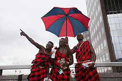 © licensed to London News Pictures. London, UK 01/01/2000. Lloyd Benson, Abrajah Rafiq and Isaac Stephen posing with an umbrella after handing out tea gift packages from Kenya to London commuters to celebrate Queen?s Diamond Jubilee this morning on London Bridge. Photo credit: Tolga Akmen/LNP