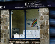 MERTHYR TYDFIL, WALES - 09 MAY 2020: A funeral services shop window with a grave stone next to a sign thanking the NHS and key workers.
