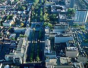 Nederland, Utrecht, Catherijnebaan, 17-10-2003; luchtfoto (25% toeslag); de Catherijnebaan was ooit een singel maar het water is gedempt in het kader van de aanleg van de cityvormomg rond de aanleg van Hoog Catherijne; in het kader van de stadontwikkeling zal het water Weer terugkeren; onder: de passage van het winkelcentrum met links en rechts van de weg kantoren; rechts boven het verkeerpleintje het Moreelsepark (met het bakstenen hoofdkantoor van de NS, Nederlandse Spoorwegen); links van het pleintje de Mariaplaats, met conservatorium; onder rechts busstation.(zie ook andere luchtfoto's).<br /> Foto Siebe Swart
