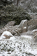 Snow falling on stones set in the Japanese style, Asticou Azalea Garden, Northeast Harbor, Maine.
