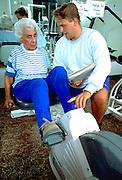 Trainer age 25 with woman age 80 on Biking machine at Lynwood Recreation Center.  St Paul Minnesota USA