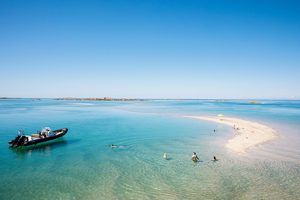 Tourists swimming & enjoying the crystal clear calm water and sandbanks at the Minquiers in Jersey CI in summer