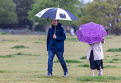 Licensed to London News Pictures. 13/05/2021. London, UK. Members of the public brave the weather on Wimbledon Common in south west London this morning as miserable May continues with grey skies and rain with temperatures down to 12c today. Weather forecasters predict sunshine and showers for most of the weekend and next week with chilly nights in the South East. Photo credit: Alex Lentati/LNP