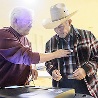 """020315  Adron Gardner/Independent<br /> <br /> Election worker Dennis Saturno, left, affixes an """"I Voted"""" sticker to the shirt of Alton Brite after he casts his vote at the Larry Brian Mitchell Recreation Center in Gallup Tuesday."""