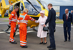 Queen Elizabeth II meets crew members with her grandson, the Duke of Cambridge as the Duke of Edinburgh follows during a visit to the new base of East Anglian Air Ambulance at Cambridge Airport.