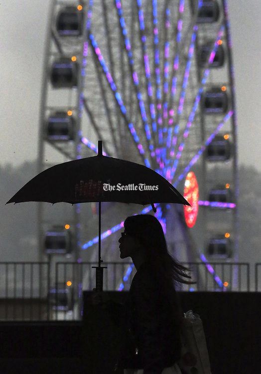A pedestrian along First Avenue in downtown Seattle passes the Seattle Great Wheel, which offers a little color on a rainy day, <br /> <br /> Ken Lambert / The Seattle Times