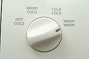 detail of washing machine knob set to warm warm