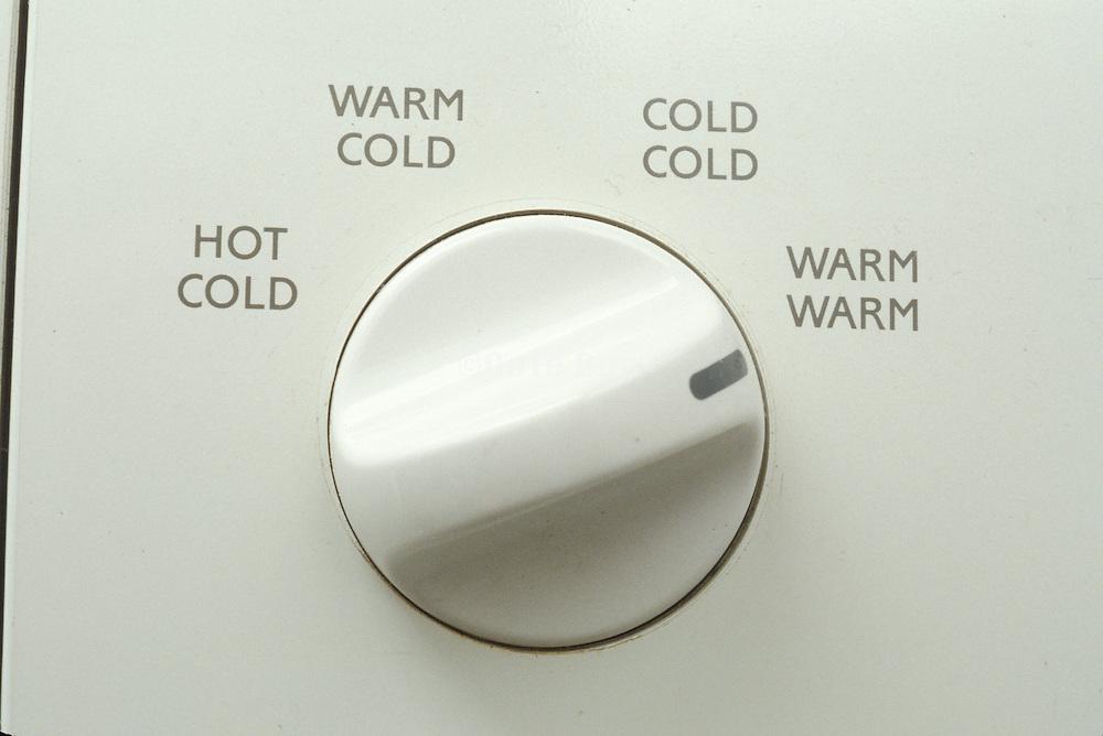 detail of washing machine knob set to warm warm
