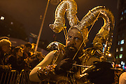 New York, NY, October 31, 2013. A man with curved, gilt horns and a gilt bow in the Greenwich Village Halloween Parade.