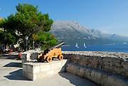 Cannon in Korcula, overlooking the Peljeski Kanal, toward the Peljesac Peninsular (Croatian mainland). Korcula old town, island of Korcula, Croatia