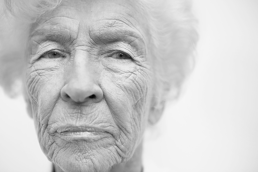 Black and white portrait photograph of anxious old granny who is frightened of an uncertain future