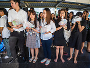 """29 NOVEMBER 2016 - BANGKOK, THAILAND:  People pray before donating alms to Buddhist monks at a special """"tak bat"""" or merit making ceremony in the Ratchaprasong skywalk of the Bangkok BTS system. The tak bat was to honor Bhumibol Adulyadej, the Late King of Thailand. Food and other goods were given to the monks, who in turn gave the items to charities that will distribute them to Bangkok's poor. More than 100 Buddhist monks participated in the merit making ceremony. The ceremony was organized by the merchants in the Ratchaprasong Intersection, which includes some of Bangkok's most upscale shopping centers.     PHOTO BY JACK KURTZ"""