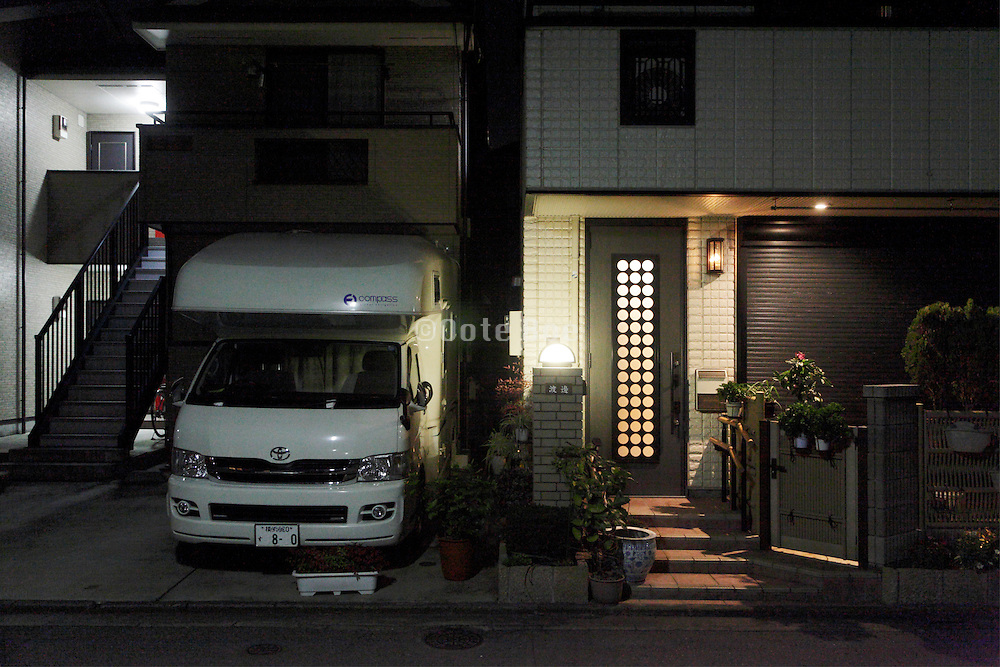 camper car parked in front of house at night