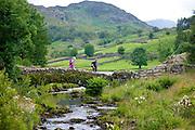 Walkers cross Packhorse Bridge across mountain stream at Watendlath in the Lake District National Park, Cumbria, UK