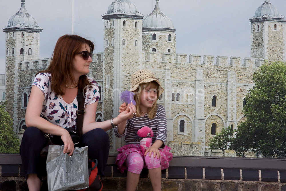 A woman sits in the shade with a young girl during a daytrip to the Tower of London. Resting in front of the illustration showing one of the world's well-known tourist attractions, the lady and girl enjoy a quiet moment among the throng of visitors to the UK capital. Her Majesty's Royal Palace and Fortress, known as the Tower of London, is a historic castle located on the north bank of the River Thames in central London. It was founded towards the end of 1066 as part of the Norman Conquest of England. The White Tower, which gives the entire castle its name, was built by William the Conqueror in 1078, and was a resented symbol of oppression, inflicted upon London by the new ruling elite.